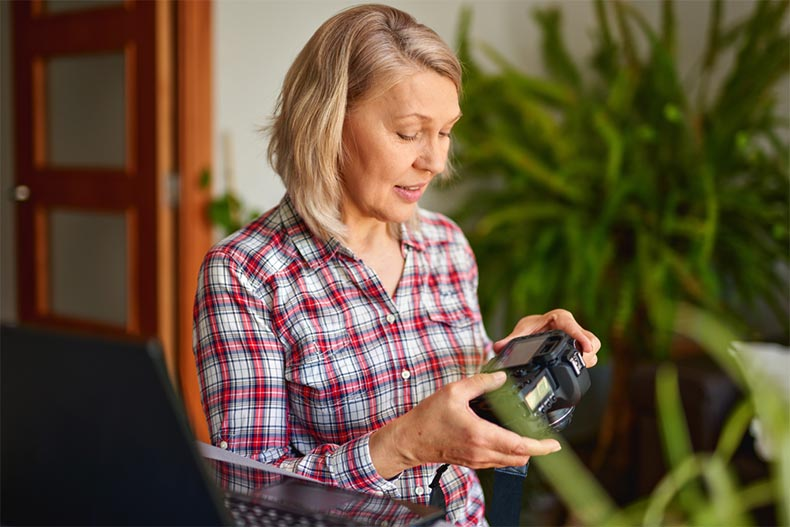 A senior woman photographer holding a professional camera