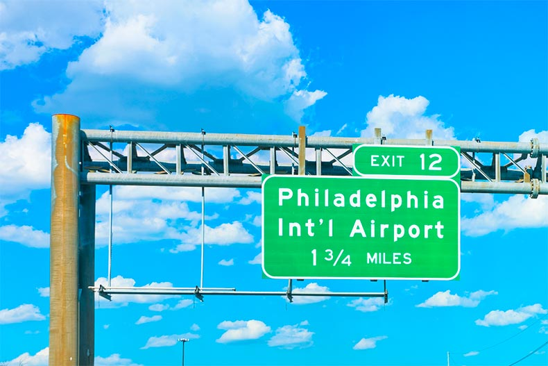 Highway sign indicating Philadelphia International Airport exit is soon