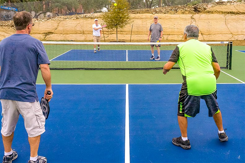 Four older adults playing pickleball on court in Kissing Tree, Texas
