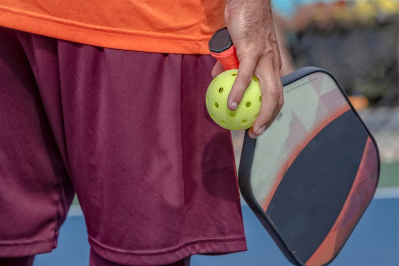 Older man in bright clothes holds pickleball paddle and ball in one hand