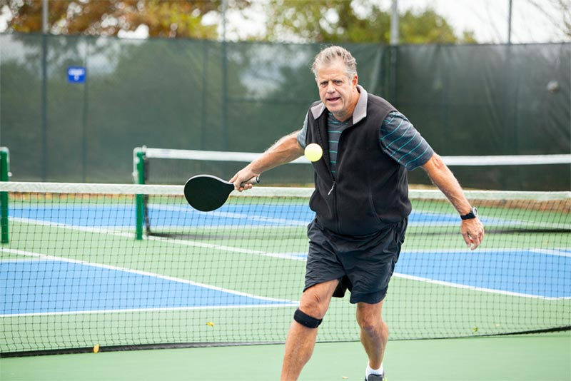 man playing pickleball on sports courts
