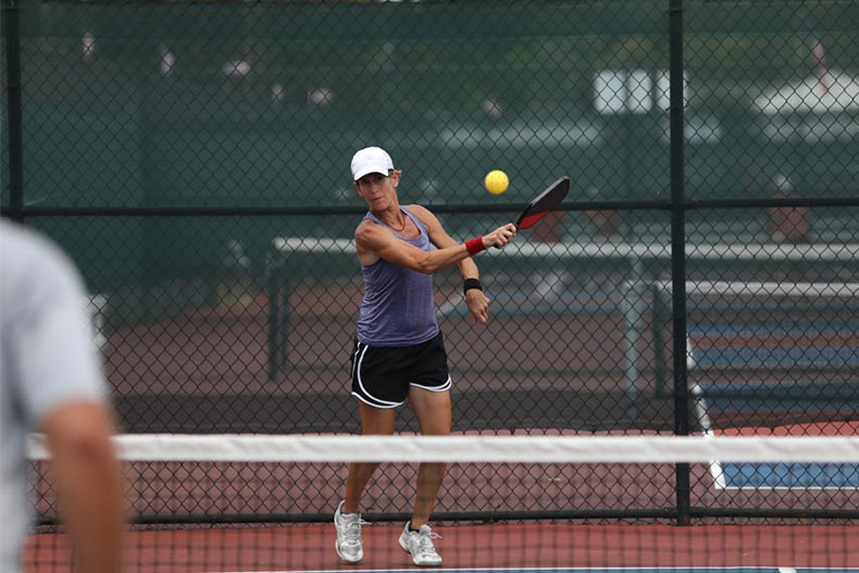 A female player hits a pickleball as she plays in a tournament