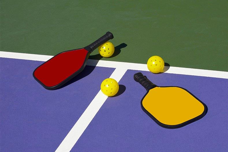 Pickleball racquets and ball on a pickle ball court.