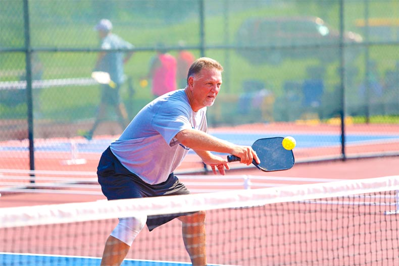 Baby boomer hitting pickleball with paddle
