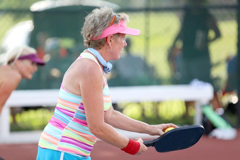 An active adult pickleball player prepares to serves as she competes in a tournament
