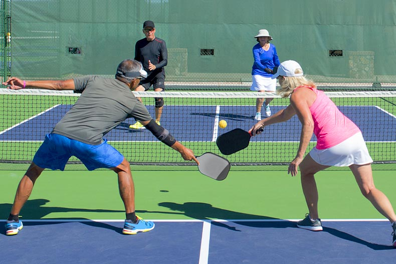 Active adults playing a doubles game of pickleball on a colorful court