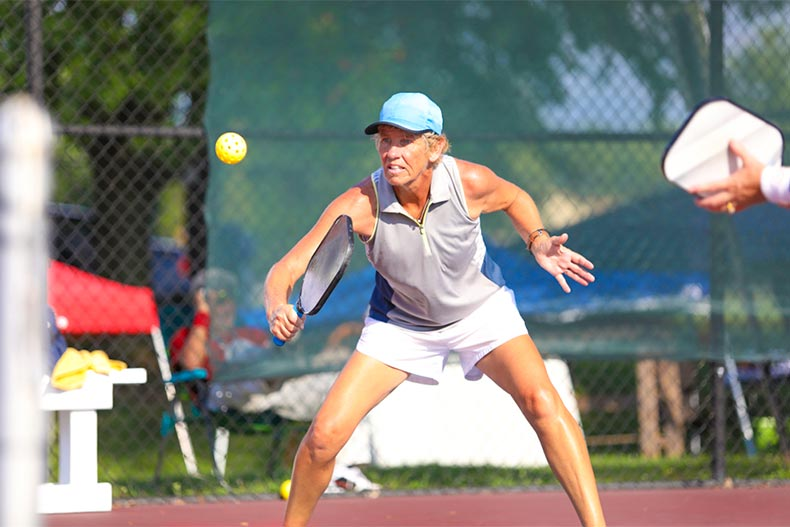Senior woman playing pickleball on a sunny day