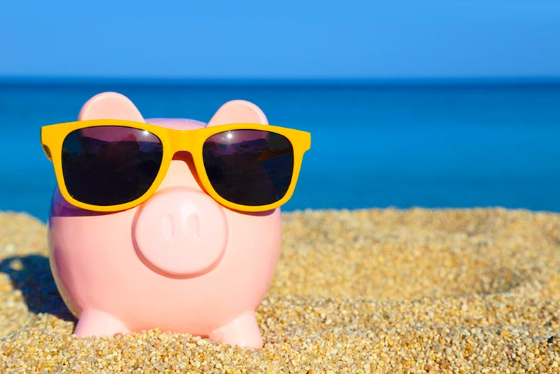 piggy bank on the beach wearing sunglasses.