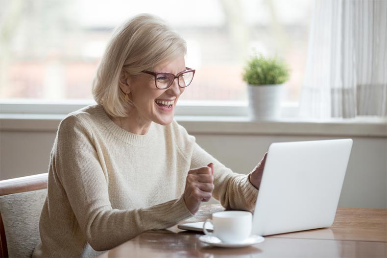 A senior woman sitting at a table and smiling at her laptop while browsing Pinterest