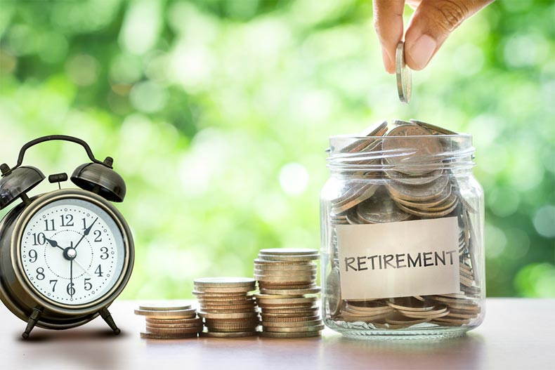 "A hand dropping a coin in a jar labeled ""retirement"" beside an alarm clock"