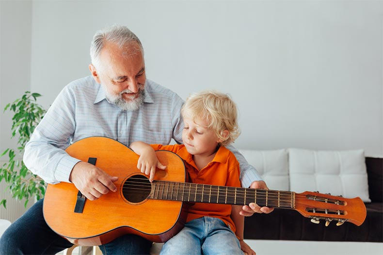 A senior man teaching a young boy to play guitar