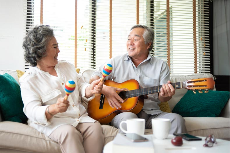 Older couple playing guitar and maracas on the couch
