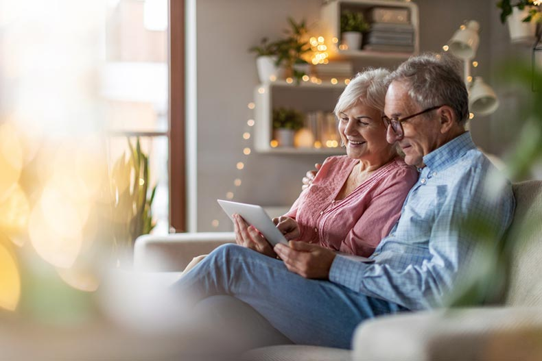 A senior couple in their living room perusing loan options on a tablet