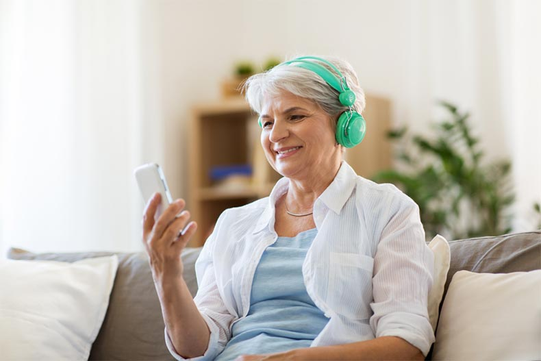 A senior woman with green headphones sitting on a couch and listening to her favorite podcast
