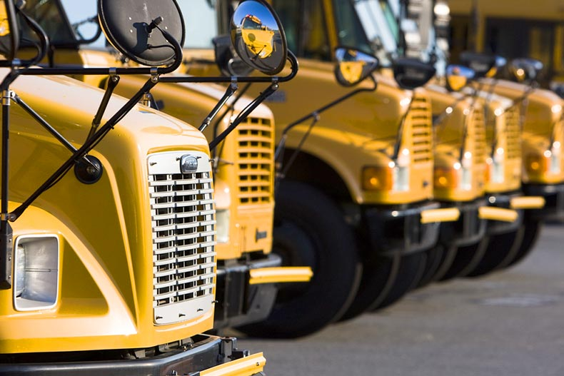 School busses sitting in a parking lot