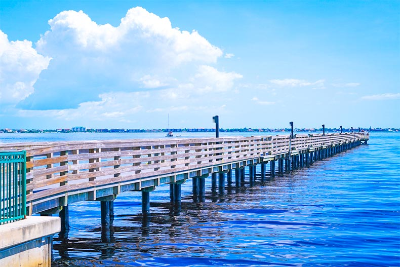 A pier over blue water and under blue skies in Port Charlotte, Florida