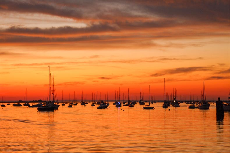 Sunset over Port Jefferson with boats on the water in Long Island