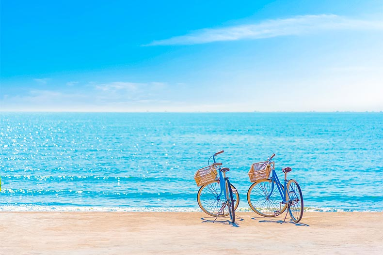 Two bicycles on a beach with sparkling blue water and sky