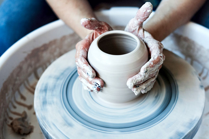Close-up of hands working on a clay pot in a ceramics studio.