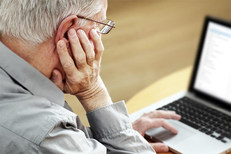 An older man with his chin resting on his hand as he researches moving companies on his laptop