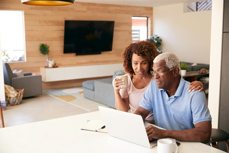 An active adult couple looking at new construction homes for sale online