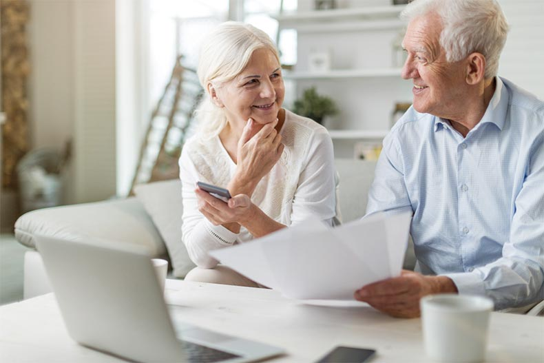 An older couple smiling at each other as they work to better protect themselves from financial scams