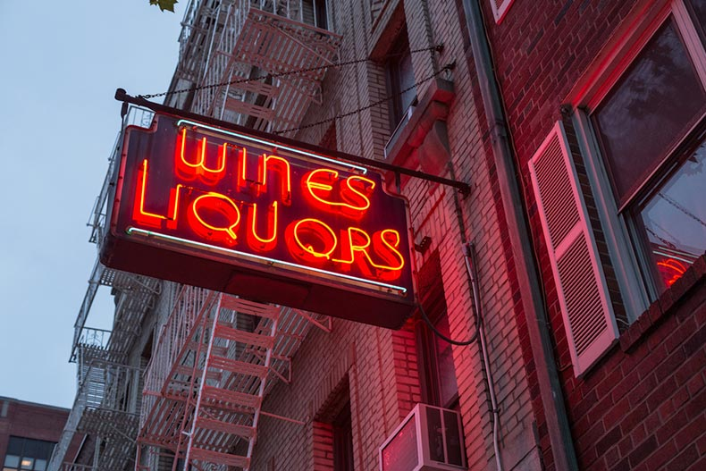 A liquor store's neon sign with a brick building in the background