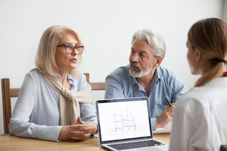 An active adult couple consulting with a salesperson about purchasing a new construction home
