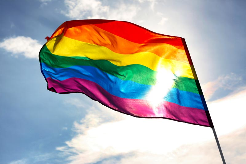 LQBTQ flag waving in blue sky