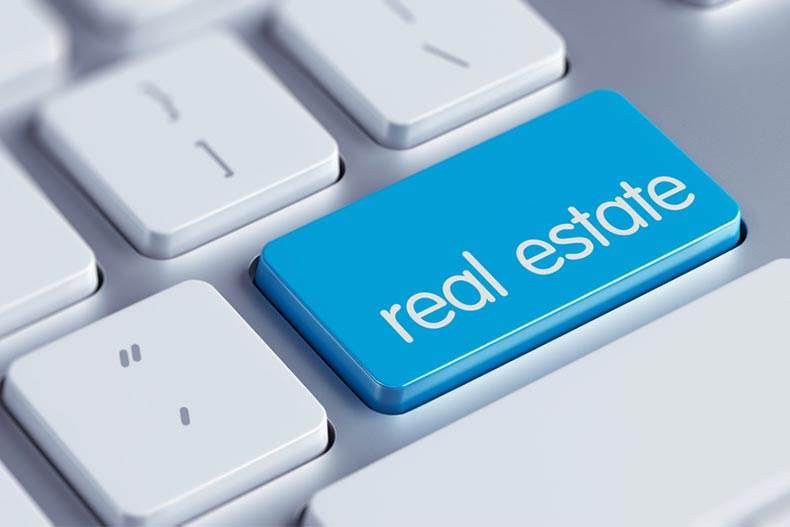 "Closeup of a blue key marked ""real estate"" on a keyboard"