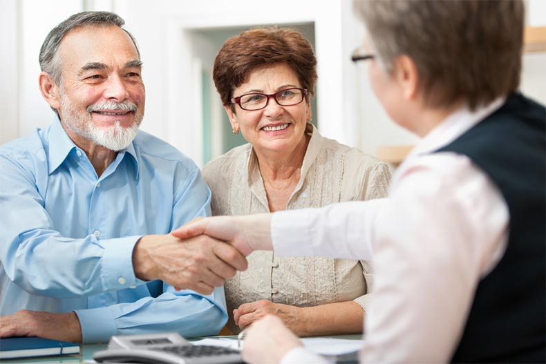 A senior couple shaking hands with a real estate agent after buying a home in a 55+ community