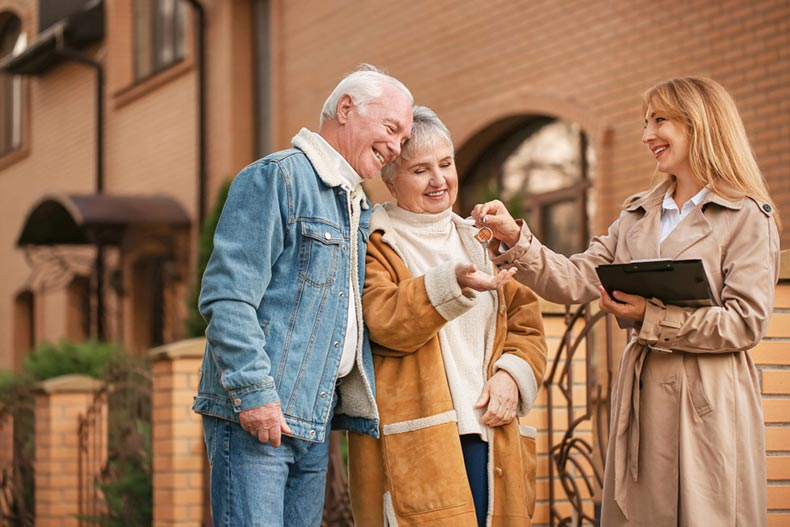 A real estate agent handing a senior couple the keys to their new home