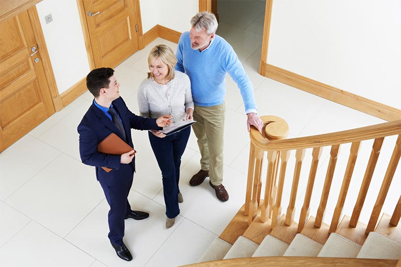 A realtor showing an active adult couple around a new construction house for sale
