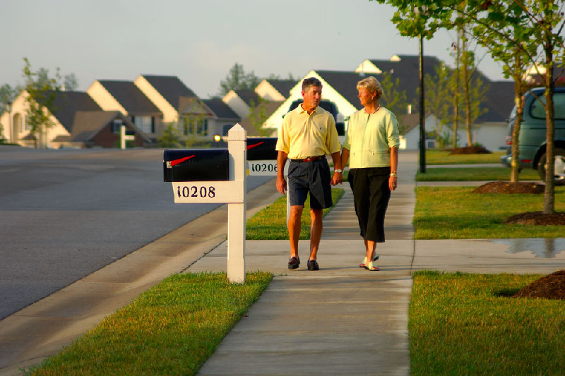 older couple walking down community sidewalk with homes and street behind them