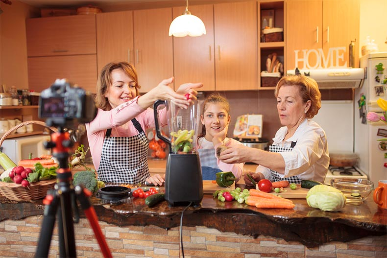 Two women and young girl recording themselves making food in a kitchen.