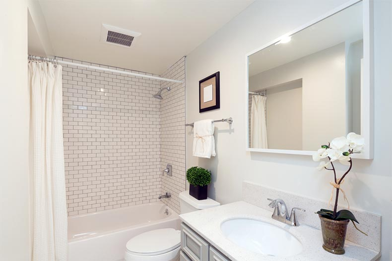 A remodeled bathroom with fresh white furnishings