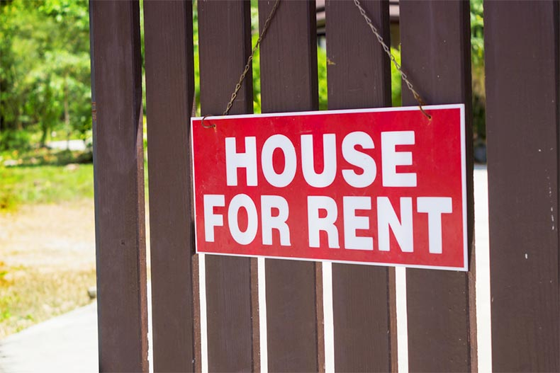 "A sign reading ""House for Rent"" hanging on a wooden fence"