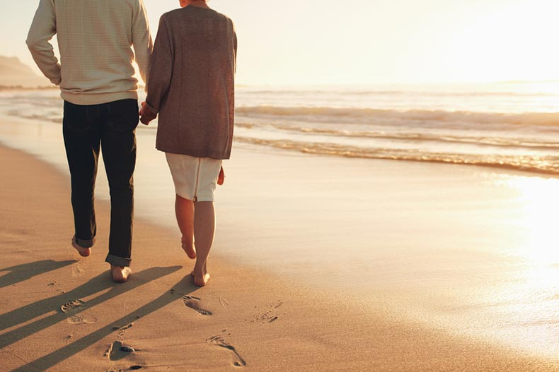 Rear view of a senior couple holding hands while walking on a beach at sunset.