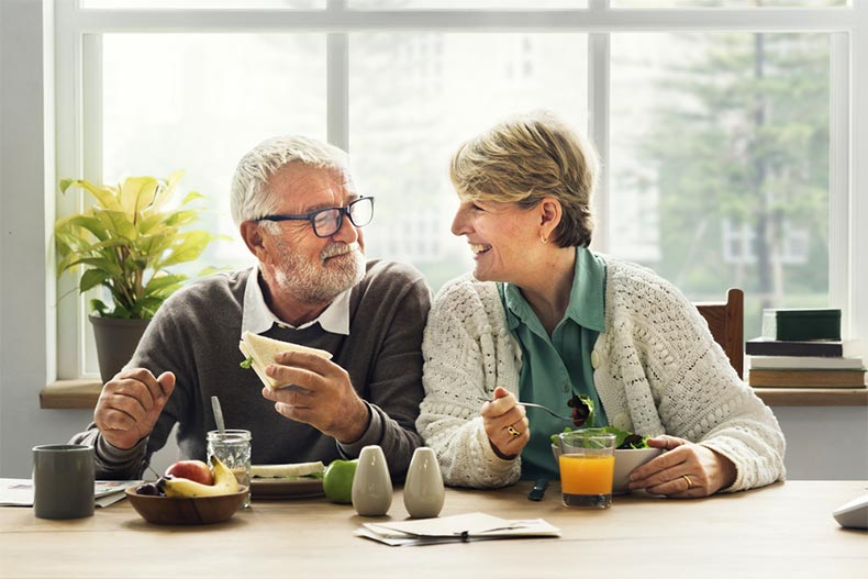 Retired senior couple smiling while having breakfast together