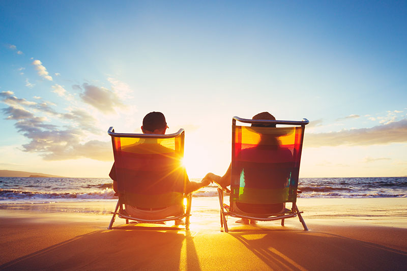 Couple sitting in beach chairs staring at ocean and sunset.