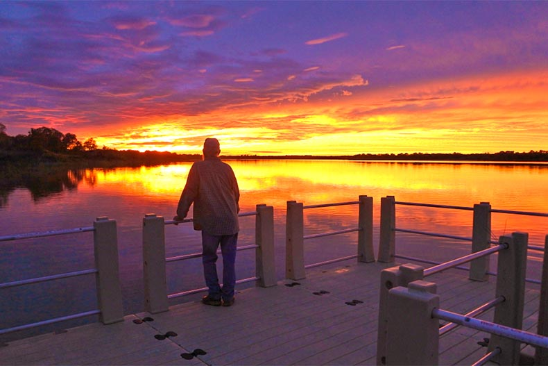 Older man on a dock looking over a lake during a colorful sunset