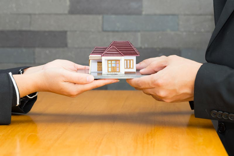two people holding a miniature home model to represent mortgage concept