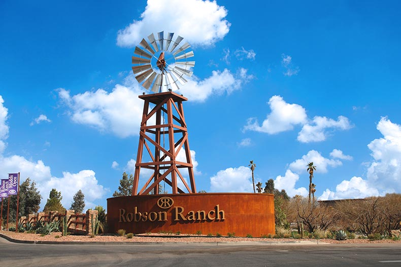 A wooden windmill behind the community sign for Robson Ranch - Arizona in Eloy, Arizona