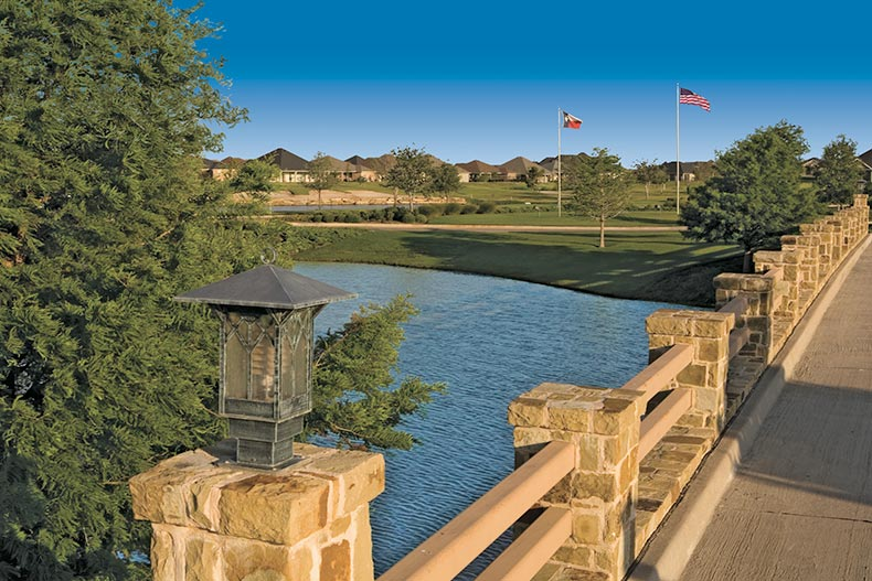 A stone bridge over a pond beside the golf course at Robson Ranch in Denton, Texas