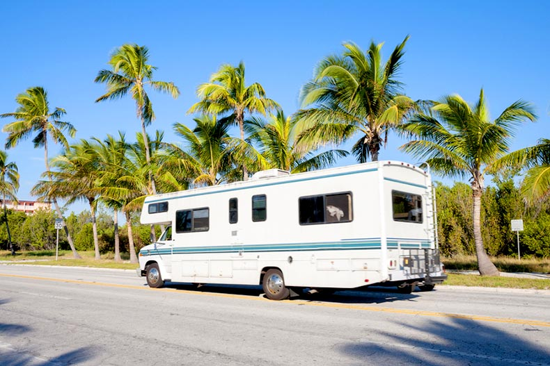 Blue sky over an RV on the road in Key West, Florida with palm trees in the background