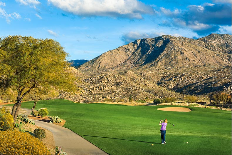 Woman golfing on the Saddlebrooke golf course surrounded by scenic mountains.