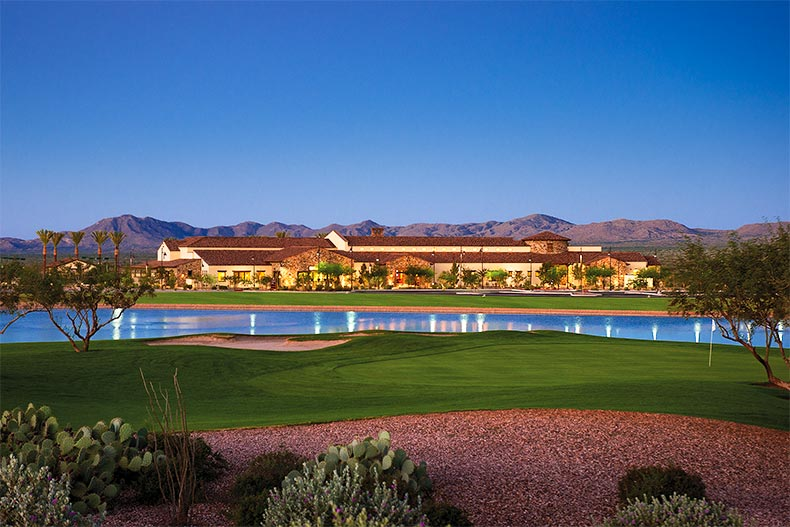 View of the SaddleBrooke Ranch clubhouse at dusk over a pond and golf green in Oracle, AZ
