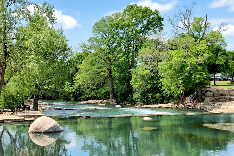 View of a green river lined with trees in San Marcos, Texas