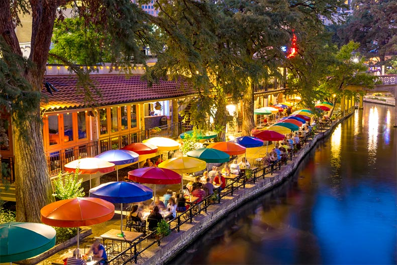 People dining along the water on San Antonio's RiverWalk