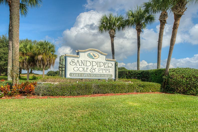 Palm trees and greenery surrounding the community sign for Sandpiper Golf & Country Club in Lakeland, Florida